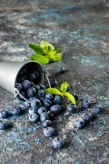 ミントの葉とミニバケツで熟したブルーベリー
