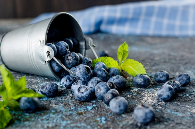 Ripe  blueberries in mini bucket with leaves mint on a dark concrete background