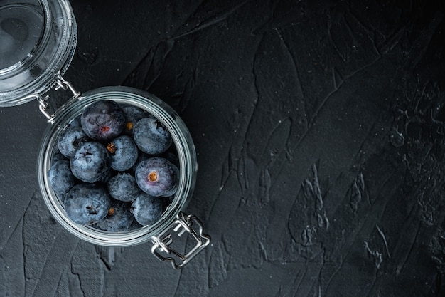 Ripe blueberry in glass jar, flat lay, on black table.