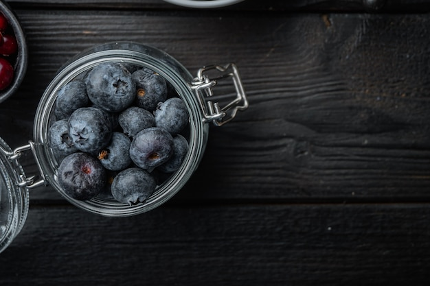 유리 항아리에 잘 익은 블루 베리, 평면 검은 나무 테이블에 누워.