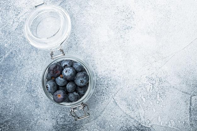 유리 항아리에 잘 익은 블루 베리, 평평하다, 질감 된 테이블에 누워.