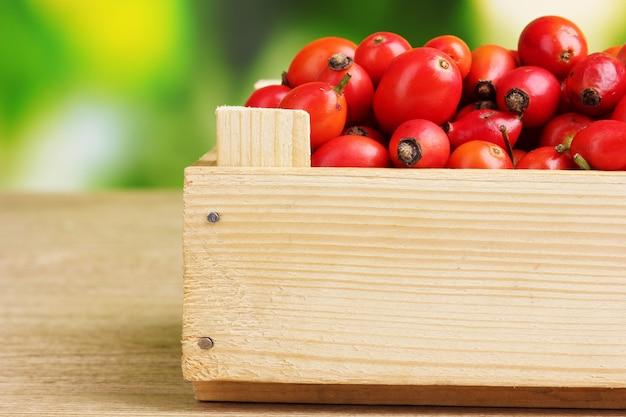 緑の木製のテーブルに木の箱に熟したブライア