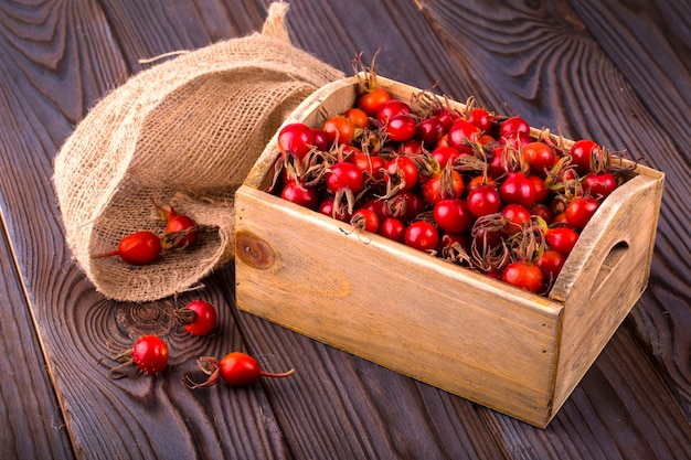 Ripe briar in wooden box and sacking on wooden table on wooden background