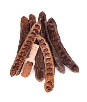 熟したイナゴマメの鞘と白い背景で隔離の豆