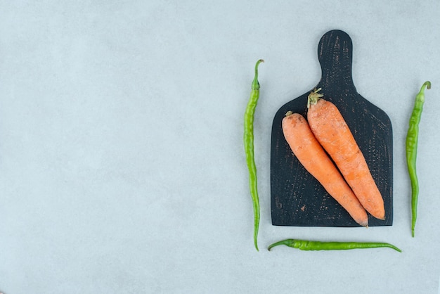 Ripe carrots and peppers on dark board.