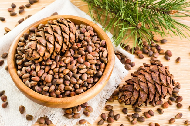 Ripe cedar cones, pine nuts and pine branches on the table