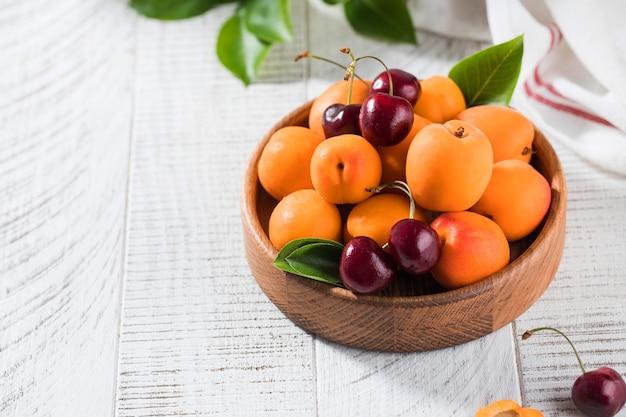 Спелые вишни и свежие абрикосы в деревянной миске на белом деревянном столе с копией пространства