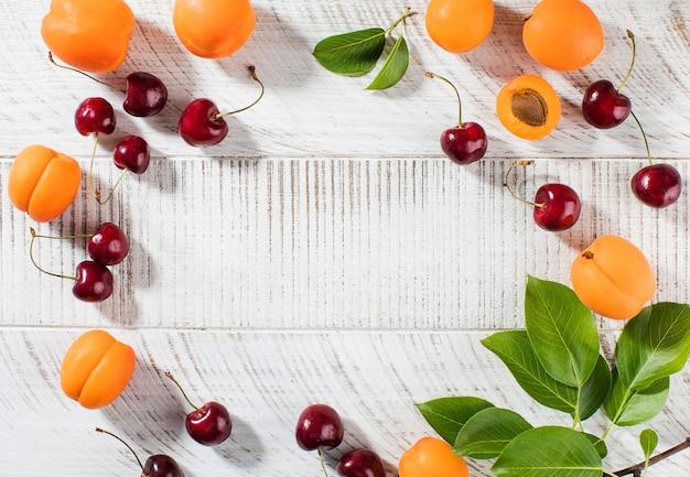 Спелые вишни и свежие абрикосы на белом деревянном столе
