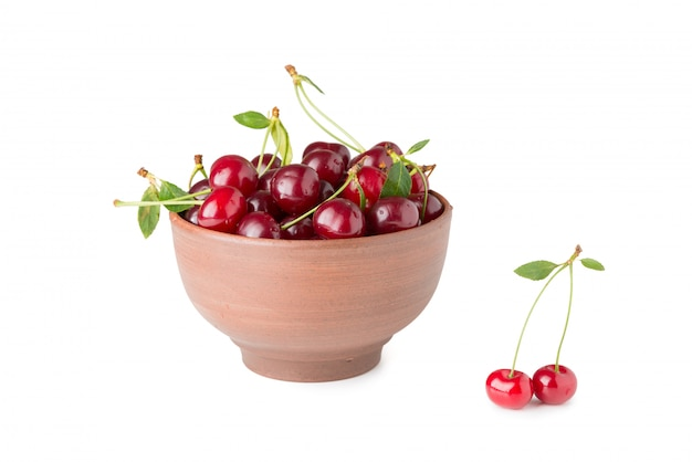 Ripe cherries in a bowl isolated on a white background