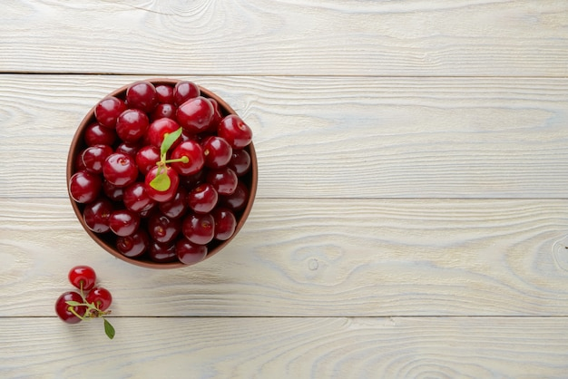 Ripe cherries in a bowl on a textured wooden background, view from above
