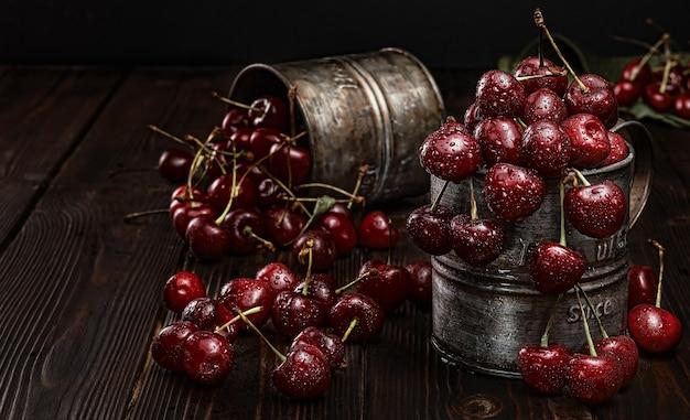 Ripe cherries in drops of water, is in vintage metal mugs. dark wood background, selective focus. fresh harvest of juicy cherries