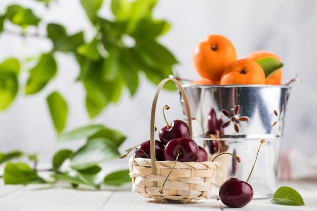 Спелые вишни в корзине и свежие абрикосы в ведре на белом деревянном столе натуральные свежие продукты