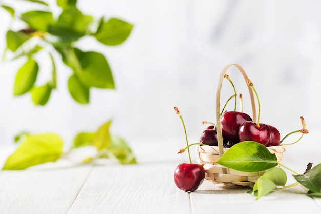 Спелые вишни в плетеной корзине на деревянном столе с копией пространства
