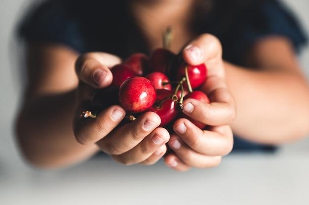 手に熟したサクランボ。ビーガン、エコ、農産物、有機食品