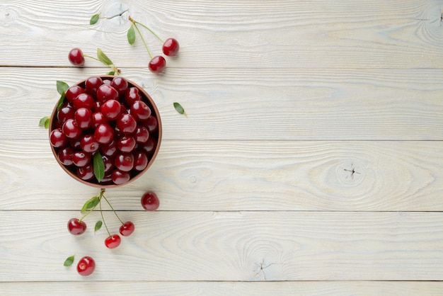 Ripe cherries and leaves in a bowl on a textured wooden background, view from above