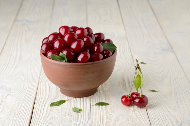 Ripe cherries and leaves in a bowl on a textured wooden background