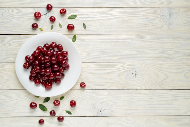 Ripe cherries and leaves in a dish on a textured wooden surface
