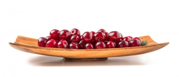 Ripe cherries and leaves in a square wooden plate isolated on a white wall