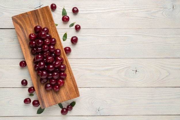 Ripe cherries and leaves in a wooden plate on a textured wooden background, view from above