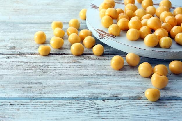 Спелые сливы на деревянном столе крупным планом
