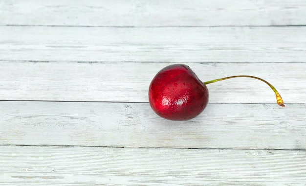 Ripe cherry on a wooden background with water drops.