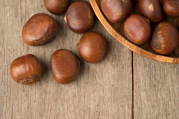 Ripe chestnuts in wooden bowl  on woden table.