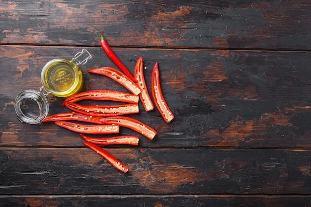 Ripe chili pepper sliced for making spicy olive oil over old dark wooden table top view