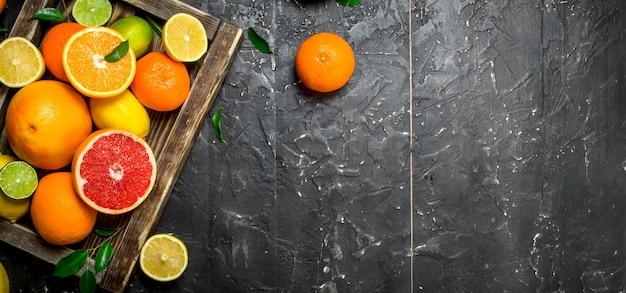 Спелые цитрусовые с листьями в лотке. на черном деревенском столе