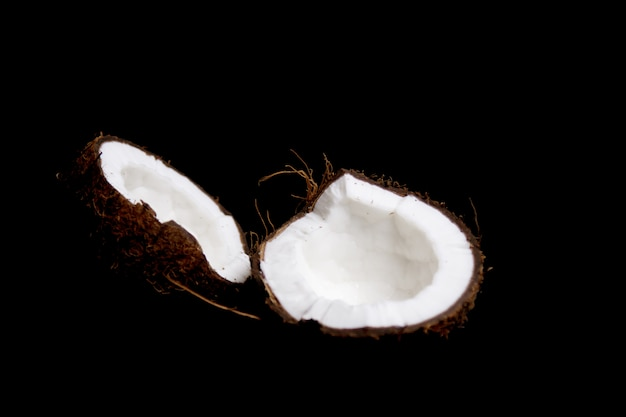 Ripe coconut is broken into two halves isolated on a black
