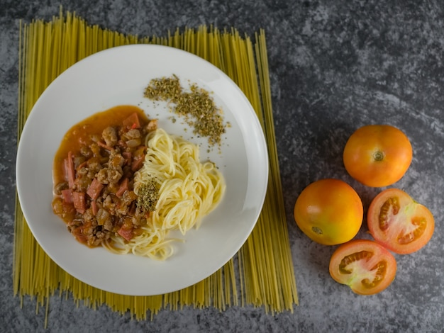 Ripe cooked pasta spaghetti tomato sauce oregano in white plate