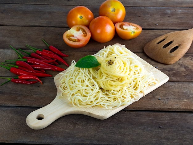 Ripe cooked pasta spaghetti on wooden chopping board