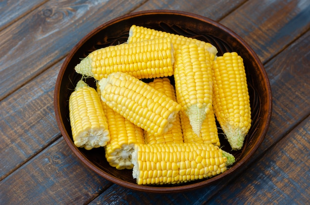 Ripe corn in a clay bowl on a dark brown wooden background.