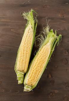Ripe corn cobs flat lay on a dark wooden table