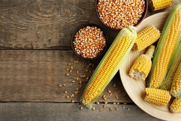 Спелая кукуруза на деревянных фоне