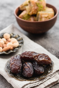 Ripe dates on metallic plate over the folded napkin