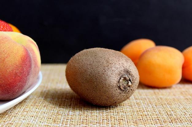 잘 익은 맛있는 갈색 키위는 검은 벽에 과일과 열매 한 접시 옆 테이블에 놓여 있습니다. 가혹한 직사광선.