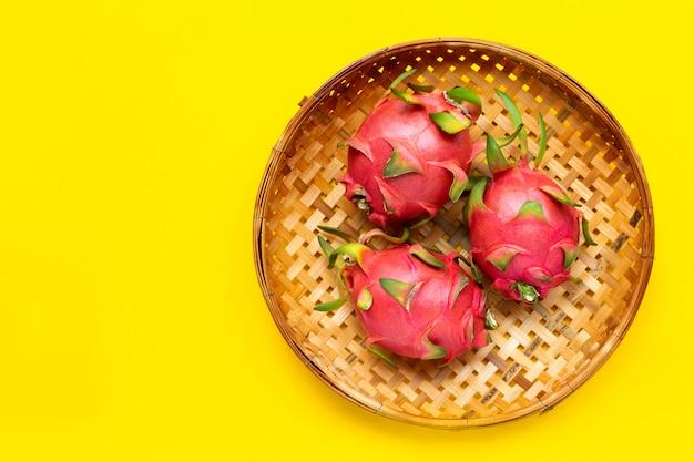 熟したドラゴンフルーツまたはピタハヤ黄色の背景に木製の竹かごを脱穀で。