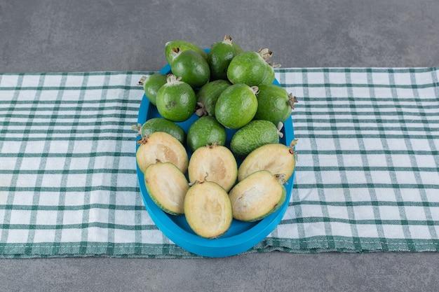 Спелые плоды фейхоа на голубой тарелке. фото высокого качества