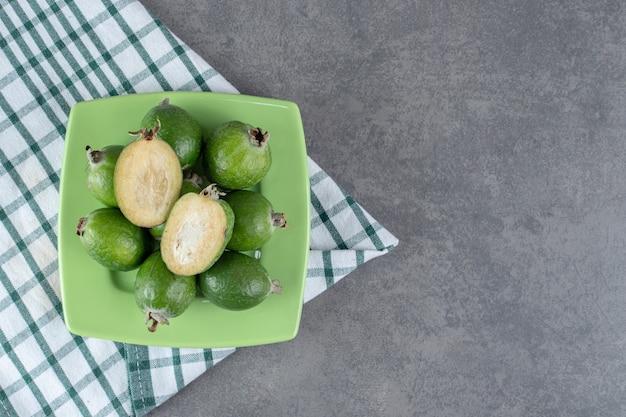 Зрелые плоды фейхоа на зеленой тарелке. фото высокого качества