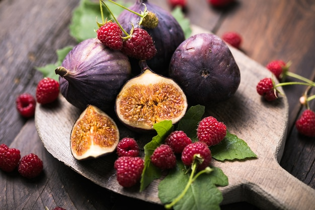 木製の背景にイチジクの葉と熟したイチジクの果実