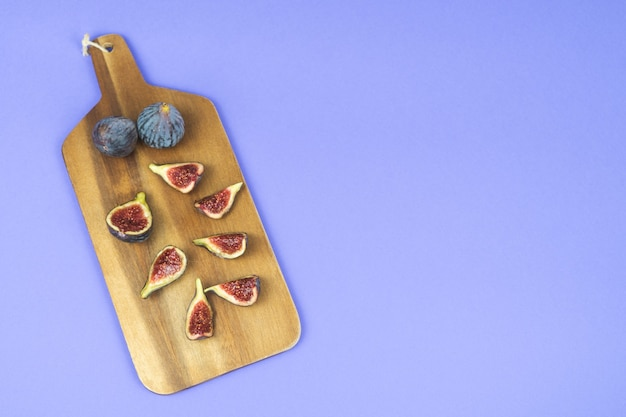 Спелый инжир нарезать на кухонном столе на синем фоне. скопируйте пространство.
