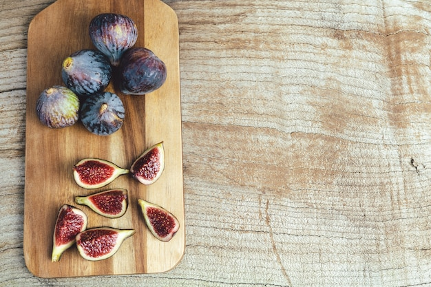 Ripe figs cut and whole on a kitchen table on a wooden base. copy space.