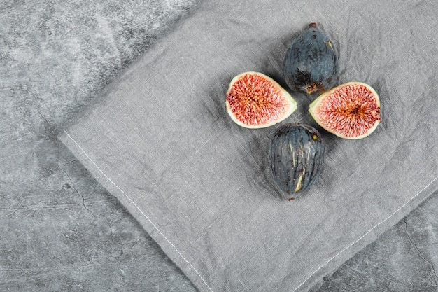 Ripe figs on a marble surface with a grey tablecloth