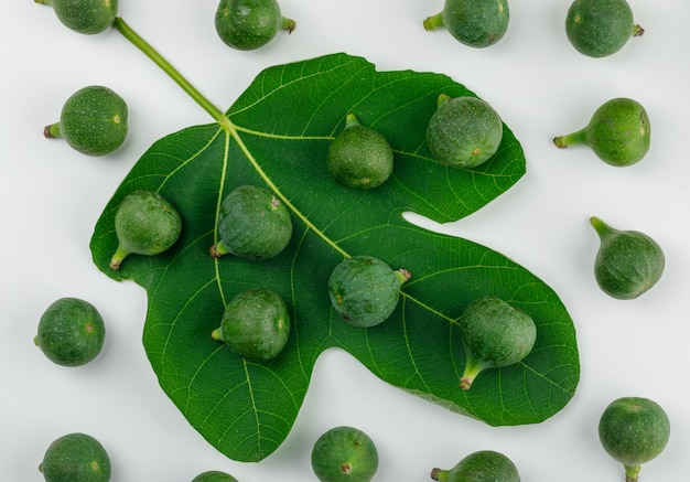 Ripe figs with leaf on white wall, flat lay.