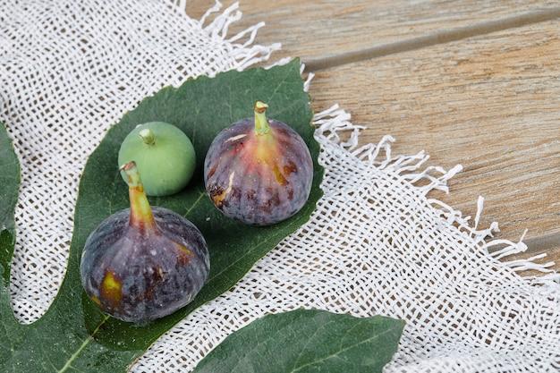 Fichi maturi con foglie e una tovaglia bianca sul tavolo di legno.