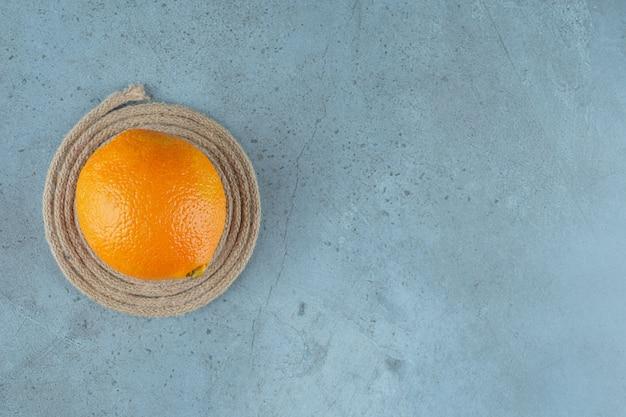 대리석 배경에 삼발이에 익은, 맛좋은 육즙 오렌지. 고품질 사진