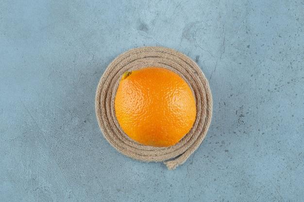 Arancia succosa matura e saporita su un sottopentola, sullo sfondo di marmo. foto di alta qualità
