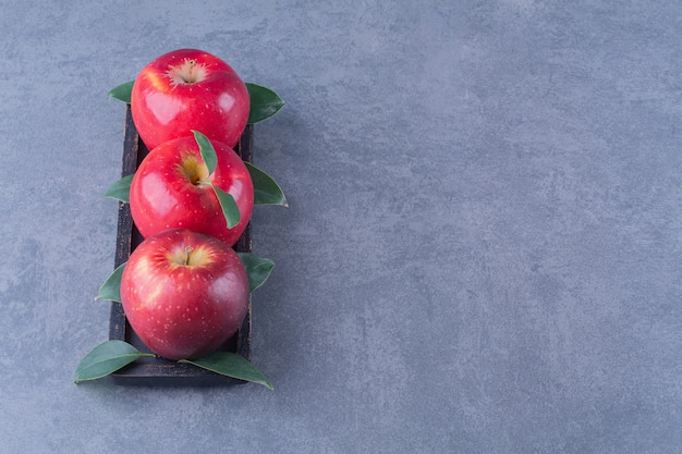 Ripe, fresh apples with leaves on wooden tray on the dark surface