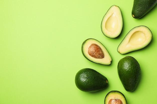 Спелый свежий авокадо на зеленом фоне, вид сверху