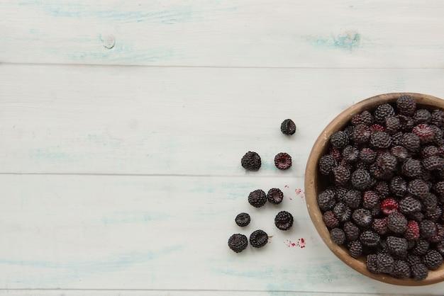 テーブルの上の木製のボウルに熟した新鮮なブラックベリー。トップビューとコピースペース